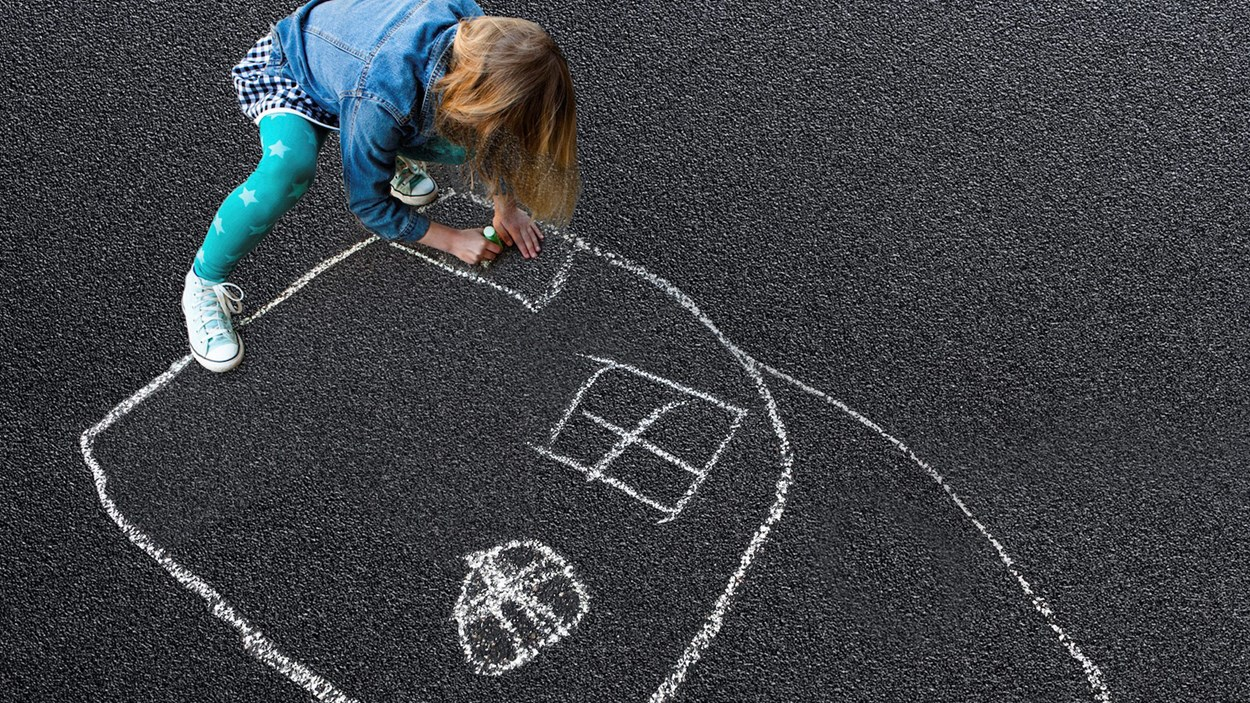 children drawing with chalk on asphalt